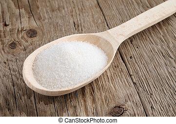 Sugar in spoon on wooden background