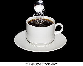 Sugar is poured from a spoon into a cup of coffee isolated...