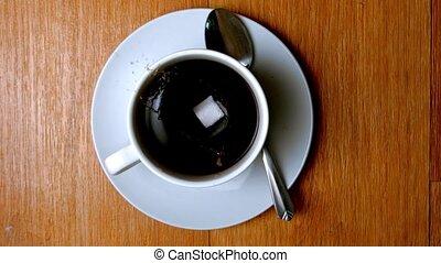 Sugar lump falling in coffee cup