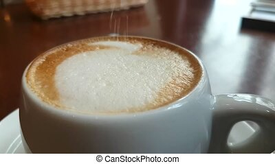 Sugar poured into a cup of cappuccino - Sugar is poured into...