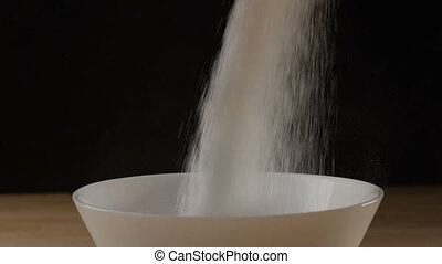 Sugar pouring into a bowl