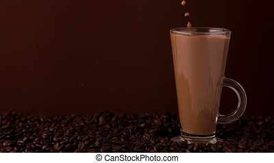 Sugar pouring into glass of coffee