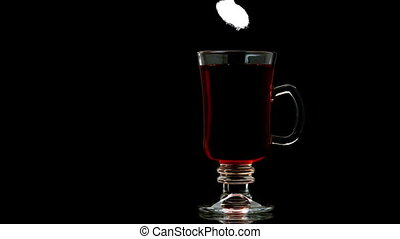 Sugar pouring into tea in a glass