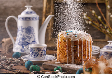 Sugar powder is poured onto the Easter cake. Still-life as a postcard to Easter. Easter decorations in a rustic style with a vintage set and an ancient frame.