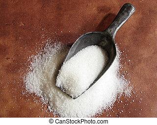 sugar scoop - scoop of granulated white sugar against brown...