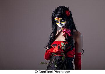 Sugar skull girl holding red rose