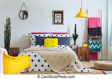 Painting of sugar skull above comfortable king-size bed with beige knit blanket. Folk bedroom concept
