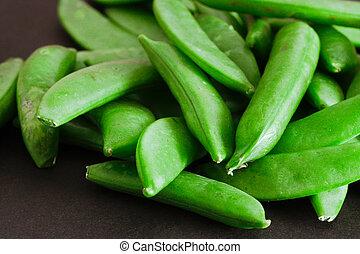 Sugar snap peas - Close up of raw sugar snap peas on a black...