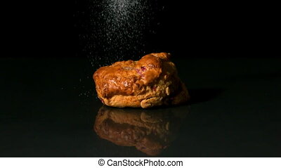 Sugar sprinkling on scone on black background in slow motion