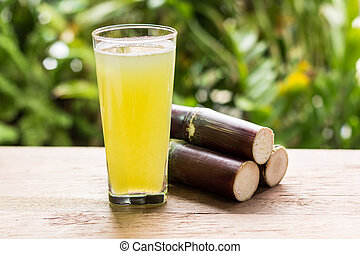 Sugarcane juice with piece of sugarcane on wooden background