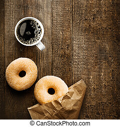 Close up overhead view of two delicious sugared ring doughnut with espresso coffee and crumpled brown paper packet on a rustic wooden surface with copyspace for a relaxing coffee break