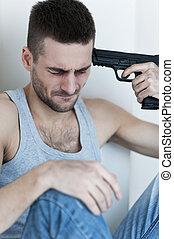 Suicide. Depressed young man sitting on the floor and holding gun near his head