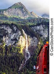 Suisse waterfall behind red firetruck vanlife camper