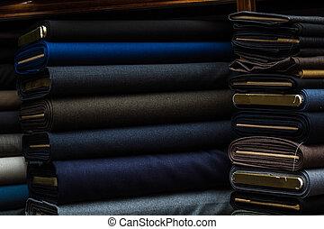 Suit fabrics with dark color on a fabric shop shelf