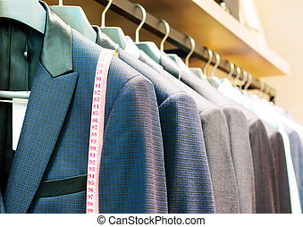 Suit - Row of men's suits hanging in closet.