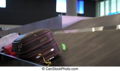 suitcase is moving on luggage conveyor belt in the airport terminal
