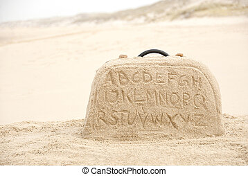 Suitcase made out of sand with alphabet