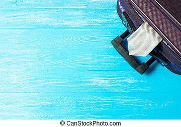 suitcase on blue wooden table with copyspace.