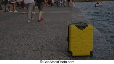 Suitcase on wheels stands on sea coast in city of Thessaloniki, Greece