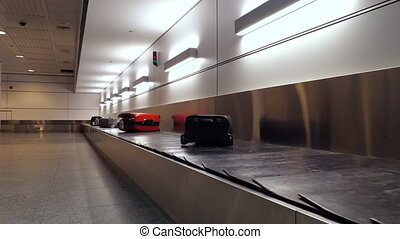 Suitcase or luggage is conveyed through the conveyor belt in arrivals lounge of airport terminal.