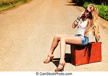 suitcase - Pretty young woman hitchhiking along a road.