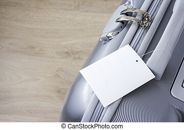 Suitcase with blank tag label on wooden floor