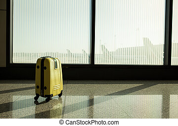 Suitcases in airport departure lounge, airplane in ...