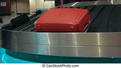 Suitcases on conveyor belt waiting for owners