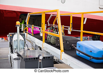 Suitcases On Moving Conveyor Attached To Airplane
