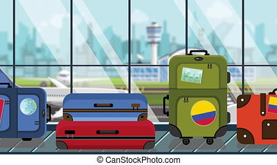 Suitcases with Colombian flag stickers on baggage carousel...
