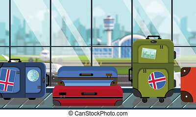Suitcases with Iceland flag stickers on baggage carousel in...
