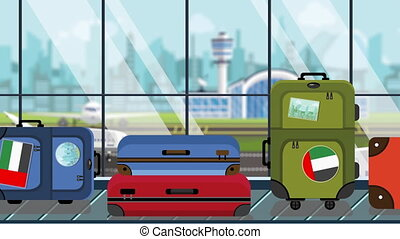Suitcases with UAE flag stickers on baggage carousel in...