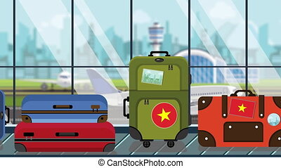 Suitcases with Vietnamese flag stickers on baggage carousel...