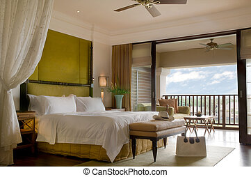 Suite bed room with balcony of a luxury resort on a sunny day