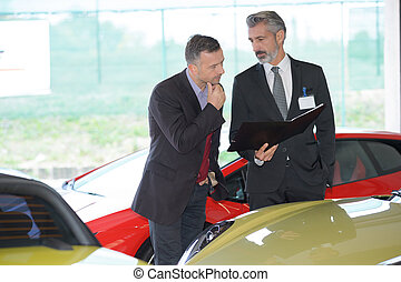 Suited car salesman in luxury forecourt