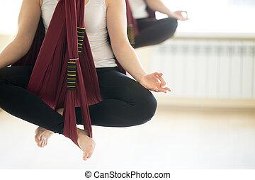 Sukhasana yoga pose in hammocks