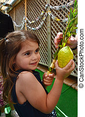 Sukkot Jewish Holiday - Jewish girl blessing on the four...