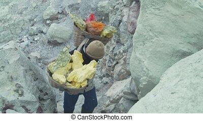 Sulfur worker, Mount Kawah Ijen volcano. - Worker carries a...
