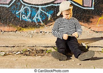 Sulking little boy sitting on a sidewalk