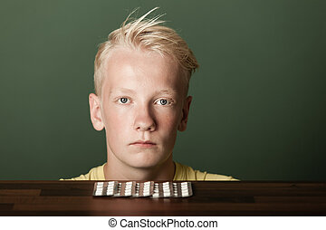 Sullen blond teenage boy with tablets in packs