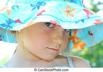 sullen look - little girl wearing a blue hat looking...