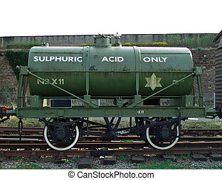 an old fashioned well used worn sulphuric acid tanker sat on rails in the sunshine.