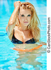 Sultry blond woman in swimming pool