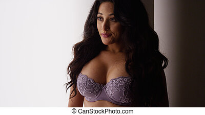 Sultry Mexican woman standing in lingerie by window