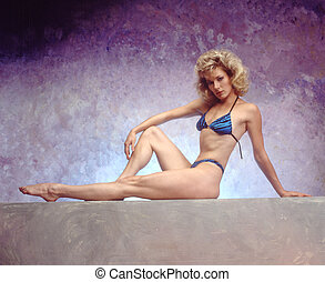 sultry vamp - Woman in Bathing suit sitting on a ledge