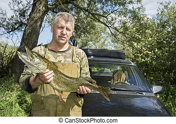 Summer a man standing near the car and holding a big pike.