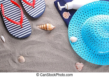 Summer accessories. Flip-flops, a towel and a hat on the sand of the sea. Top view.