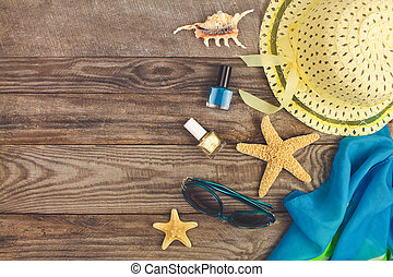 Summer accessories on wooden old background. Top view. Toned image.