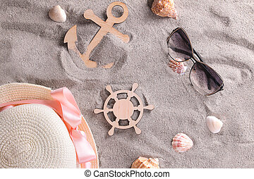Summer accessories with a decorative anchor and a steering wheel on the sand of the sea. View from above