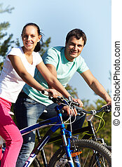 Summer activity  - Portrait of two young people on bikes